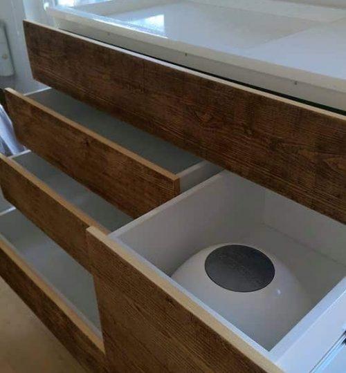 commode table à langer ouverte laissant voir la poubelle à couches et les tiroirs de rangement